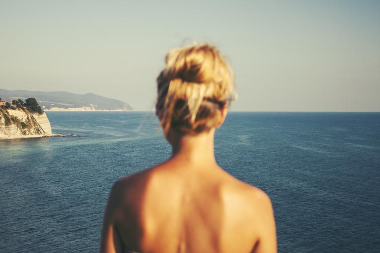 žena s blond vlasy do drdolu stojí zády a dívá se na moře, má holá záda